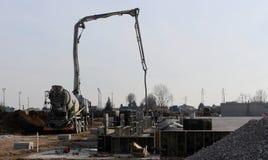 Le mélangeur concret de camion avec sa pompe établit la base d'un nouveau bâtiment Image libre de droits
