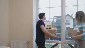 Le ménage marié avec des boîtes dans des mains regarde sur la vue en dehors de la fenêtre banque de vidéos