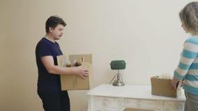 Le ménage marié avec des boîtes observe une salle légère dans la nouvelle maison banque de vidéos