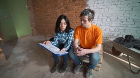 Le ménage marié dans la salle inachevée regarde dans le dessin de la future maison et de l'étreinte banque de vidéos