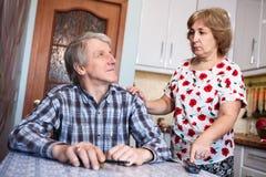 Le ménage marié par personnes âgées caucasiennes se dispute en raison de la TV dans la cuisine Photographie stock