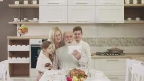 Le ménage utilise une Tablette pour la communication visuelle pendant un dîner de famille banque de vidéos