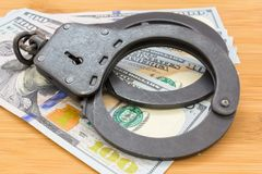 Le métal noir menotte le mensonge sur les 100 dollars de billets de banque Image stock