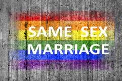 Le même mariage de sexe et le drapeau de LGBT peint sur le fond donnent au béton une consistance rugueuse gris Images stock