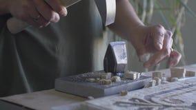 Le maître à l'aide d'un marteau et d'une enclume fait une pièce pour faire la vidéo de panneaux banque de vidéos