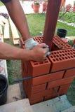 Le maître au chantier de construction étend une pose de brique images libres de droits