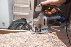 Le maître coupe le bois avec une scie de gabarit Photos stock