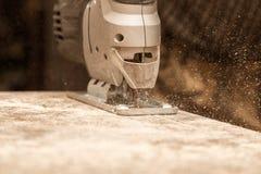Le maître coupe le bois avec une scie de gabarit Images stock