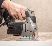 Le maître coupe le bois avec une scie de gabarit Image libre de droits