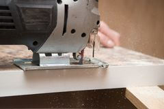 Le maître coupe le bois avec une scie de gabarit Images libres de droits
