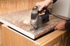 Le maître coupe le bois avec une scie de gabarit Photo stock