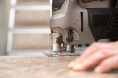 Le maître coupe le bois avec une scie de gabarit Photo libre de droits
