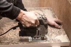 Le maître coupe le bois avec une scie de gabarit Photographie stock libre de droits