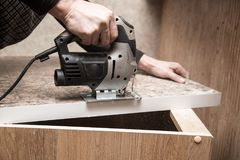 Le maître coupe le bois avec une scie de gabarit Photos libres de droits