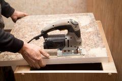 Le maître coupe le bois avec une scie de gabarit Photographie stock