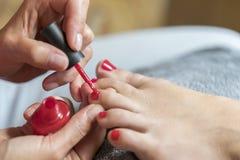 Le maître couvre les clous du client de vernis Les mains dans les gants s'inquiète des clous du pied d'une femme Pédicurie, beaut images stock
