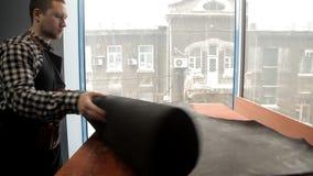 Le maître déroule un rouleau de cuir pour la production des marchandises en cuir banque de vidéos
