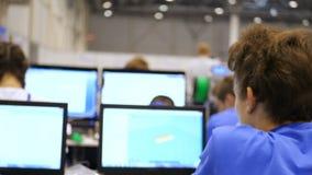 Le maître d'école élémentaire aide des étudiants avec des ordinateurs Un groupe d'écoliers soulevant leurs mains dans la classe banque de vidéos