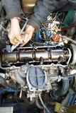 Le maître dans le garage tape les valves dans la vieille voiture, une vieille voiture usée photo libre de droits