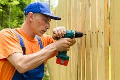 Le maître de bâtiment avec la machine de vis construit une barrière en bois Photographie stock