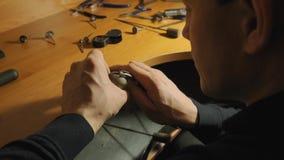 Le maître de bijou finit la décoration de l'anneau argenté avec le puttin la pierre gemme dans un mouvement lent de couronne supé banque de vidéos