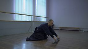 Le maître de kendo fait un arc à l'épée du ` s de katana dans les étagères avant lui, puis l'élève et s'habille sur la ceinture banque de vidéos