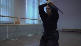 Le maître de kendo s'exerce avec l'épée dans la fierté de Halloween banque de vidéos