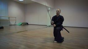 Le maître de Kendoka fait des oscillations par l'épée katan dans la fierté, exécute le kata dans la salle de gymnastique avec des banque de vidéos