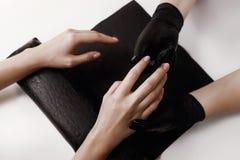 Le maître de la manucure dans les gants noirs, fait le massage hydratant, nourrissant le client crème photos stock