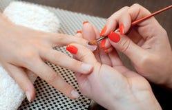 Le maître de la manucure fait le gel de prolongements d'ongle dans le salon de beauté Images stock
