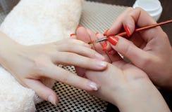 Le maître de la manucure fait le gel de prolongements d'ongle dans le salon de beauté Image stock