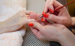 Le maître de la manucure fait le gel de prolongements d'ongle dans le salon de beauté photo stock