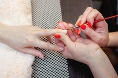 Le maître de la manucure fait le gel de prolongements d'ongle dans le salon de beauté Photos stock
