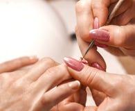 Le maître de la manucure peint des ongles Photo stock