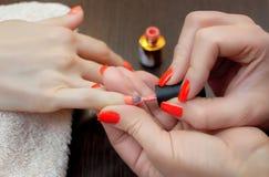 Le maître de la manucure peint des ongles avec le vernis à ongles pendant la procédure des prolongements d'ongle avec le gel Photo libre de droits