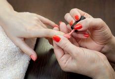Le maître de la manucure peint des ongles avec le vernis à ongles pendant la procédure des prolongements d'ongle avec le gel dans Photos stock