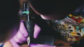 Le maître de tatouage fonctionne avec une machine de tatouage banque de vidéos