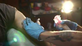 Le maître de tatouage traite le tatouage de finition avec une solution stérile et des chiffons clips vidéos