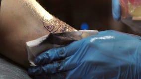 Le maître de tatouage traite le tatouage de finition avec une solution stérile et des chiffons banque de vidéos
