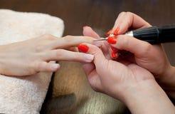 Le maître des scies de manucure et attachés qu'un ongle forment pendant la procédure des prolongements d'ongle avec le gel dans l Photos libres de droits