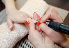 Le maître des scies de manucure et attachés qu'un ongle forment pendant la procédure des prolongements d'ongle avec le gel Images stock