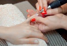 Le maître des scies de manucure et attachés qu'un ongle forment pendant la procédure des prolongements d'ongle avec le gel dans l Images libres de droits