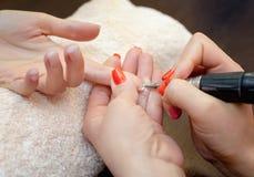 Le maître des scies de manucure et attachés qu'un ongle forment pendant la procédure des prolongements d'ongle avec le gel dans l Images stock