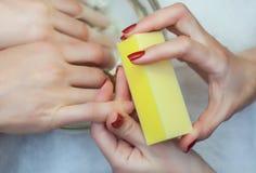 Le maître des scies de manucure et attachés qu'un ongle forment pendant la procédure des prolongements d'ongle avec le gel dans l Photo libre de droits