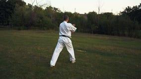 Le maître du karaté dans le kimono blanc aiguise son autorité pendant le matin de rano de parc de ville clips vidéos