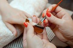Le maître du vernis à ongles met un fixatif sur le doigt avant de faire le gel d'ongles dans le salon de beauté image libre de droits