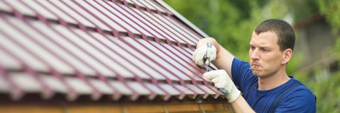 Le maître fait le travail de réparation sur le toit, vers la gauche un endroit vide pour une inscription photos stock