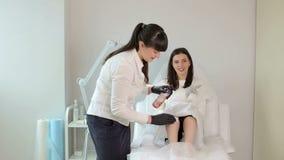 Le maître manipule des pieds dans les gants avec un tissu humide avant la procédure de dépilage banque de vidéos