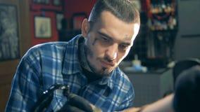 Le maître masculin tatoué fait un tatouage seul banque de vidéos