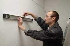Le maître mesure le mur. Photo libre de droits